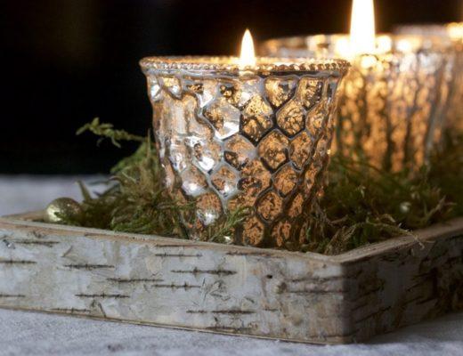 Une décoration de Noël lumineuse et natuelle, plateau en bois, mousse et photophores.