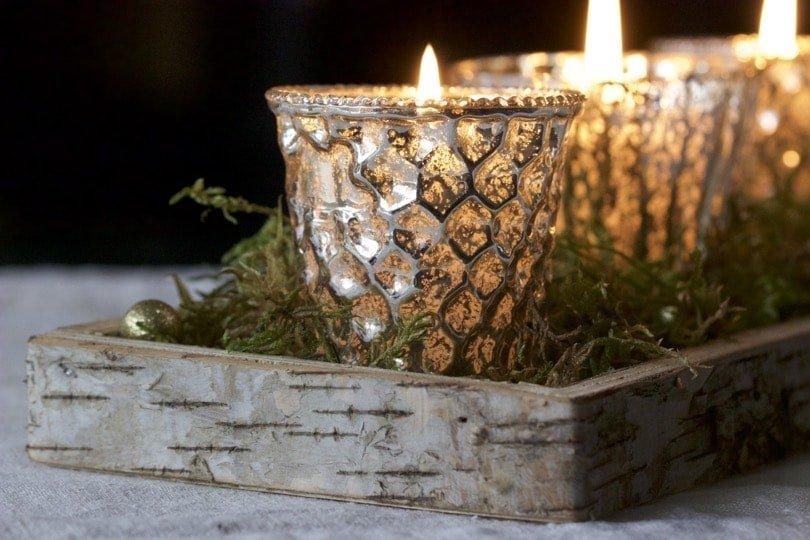 Pour une décoration de Noël lumineuse, photophores mercurisés dorés sur lit de mousse.