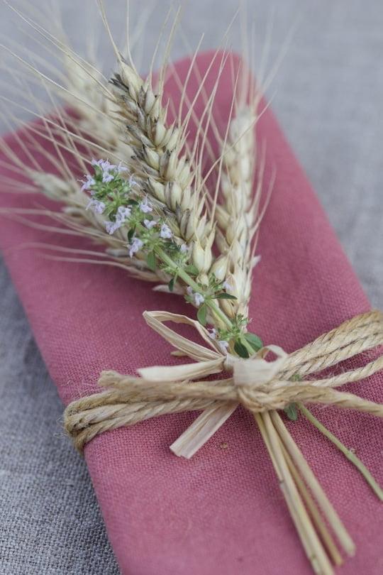 De la ficelle et du thym pour des ronds de serviette sur une table d'été champêtre.