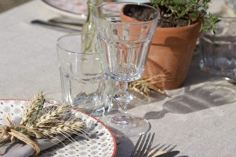 Des assiettes dépareillées et de gros verres pour une table d'été champêtre.