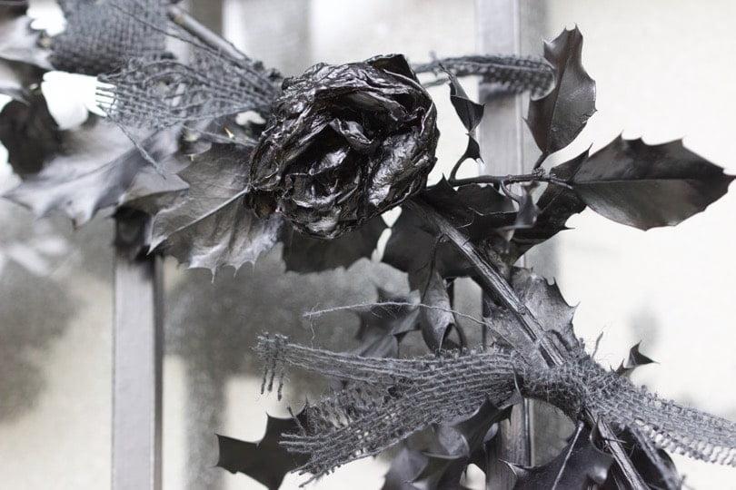 Rose fixée sur la couronne de porte pour Halloween en noir et blanc.