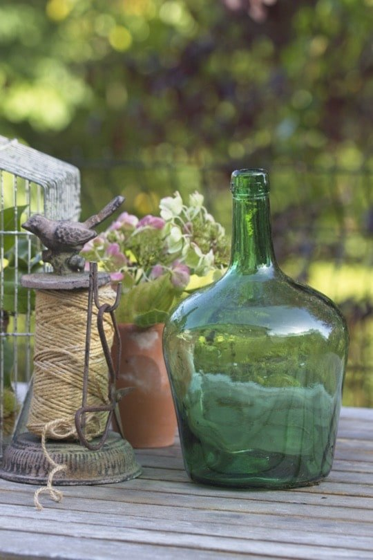 La récup' au jardin avec des pots en terre cuite et une dame jeanne